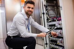 Técnico que usa a tabuleta digital ao analisar o servidor imagem de stock