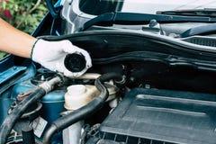 Técnico que verifica o serviço do carro, ruptura do óleo no carro do motor imagem de stock