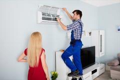 Técnico Repairing Air Conditioner em casa Foto de Stock