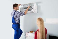 Técnico Repairing Air Conditioner em casa Imagens de Stock Royalty Free