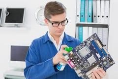 Técnico sonriente que trabaja en el ordenador quebrado Fotografía de archivo