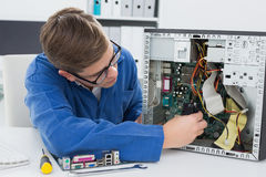 Técnico sonriente que trabaja en el ordenador quebrado Imagen de archivo