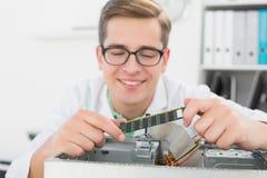 Técnico sonriente que trabaja en la CPU quebrada Imagenes de archivo