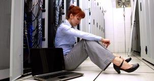 Técnico subrayado que se sienta en piso al lado del servidor abierto almacen de video