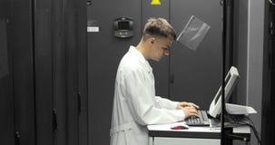 Técnico Works de las TIC en un compuiter en centro de datos grande por completo de servidores del estante Él funciona con los dia almacen de metraje de vídeo