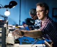 Técnicos bondes que trabalham nas peças da eletrônica imagem de stock royalty free