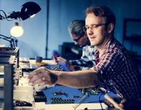 Técnicos bondes que trabalham nas peças da eletrônica foto de stock