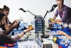 Técnicos bondes que trabalham nas peças da eletrônica do robô fotografia de stock