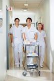 Técnicos com carro médico que andam no corredor Foto de Stock Royalty Free