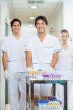 Técnicos com o carro médico no corredor do hospital Imagens de Stock
