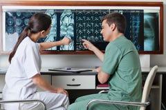 Técnicos médicos que señalan en la radiografía de MRI Imagen de archivo