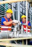 Técnicos o ingenieros asiáticos que trabajan en la válvula Imagen de archivo libre de regalías