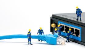 Técnicos que conectam o cabo da rede