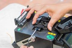 Técnicos que cortam e cabos de fibra ótica da fusão imagem de stock royalty free