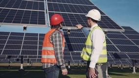 Técnicos que discutem a disposição do painel solar fora Imagens de Stock Royalty Free