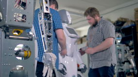 Técnicos que montan varios robots en un taller almacen de metraje de vídeo
