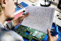 Técnicos que trabalham guardando o papel do guia do circuito da eletrônica fotos de stock