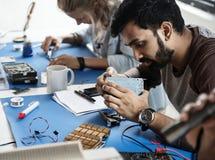 Técnicos que trabalham nas peças da eletrônica fotografia de stock