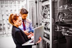 Técnicos que usam o portátil ao analisar o servidor foto de stock