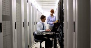 Técnicos que usan el analizador digital del cable en el servidor almacen de video
