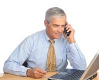 téléphone âgé de milieu d'ordinateur portatif d'homme d'affaires Photos stock
