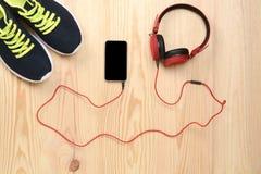 Téléphone, écouteurs et espadrilles sur le plancher Images libres de droits