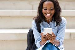 Téléphone africain d'étudiante Photo stock