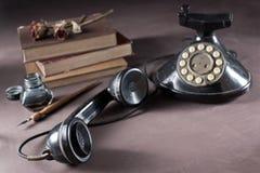 Téléphone avec le vieux livre Photos libres de droits