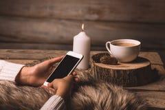 Téléphone blanc dans les mains de la fille, d'une tasse de café, d'une bougie, de la fourrure et des cônes photographie stock libre de droits
