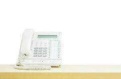 Téléphone blanc de plan rapproché, téléphone de bureau sur le bureau en bois brouillé dans le lieu de réunion sous la lumière de  Images stock