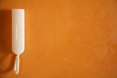 Téléphone blanc sur le mur orange Photo stock