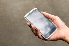 Téléphone cassé à disposition dehors Photo libre de droits