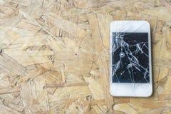 Téléphone cassé sur la table en bois Image libre de droits