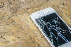 Téléphone cassé sur la table en bois Photo libre de droits