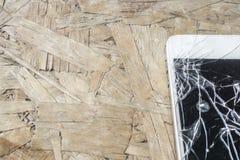 Téléphone cassé sur la table en bois Photo stock
