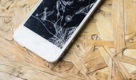 Téléphone cassé sur le bureau en bois Images stock