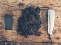 Téléphone, cheveux et tondeuses Images stock