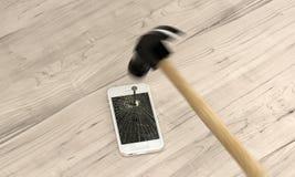 Téléphone cloué à la table avec le marteau Image stock