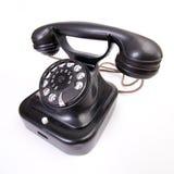 Téléphone démodé sur le support blanc photographie stock libre de droits