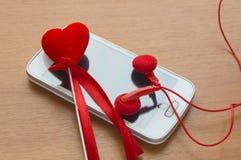 Téléphone d'écran blanc avec des écouteurs et un coeur rouge, jour du ` s de Valentine Photos libres de droits