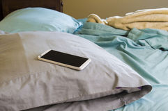 Téléphone d'Android avec un écran vide s'étendant sur un oreiller sur un lit Photographie stock