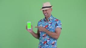 Téléphone d'apparence d'homme et de donner pouces de touristes ethniques multi heureux  banque de vidéos
