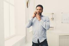 Téléphone d'homme d'affaires parlant au téléphone près de la fenêtre Image stock