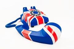 Téléphone d'Union Jack avec le récepteur outre du crochet s'étendant devant le téléphone d'isolement sur le fond blanc Images libres de droits
