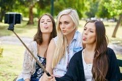 Téléphone de bâton de selfie de filles Photographie stock libre de droits