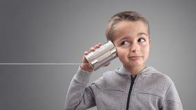 Téléphone de boîte en fer blanc écoutant de bonnes actualités curieuses photographie stock
