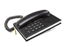 Téléphone de bureau de vieux bureau avec l'annuaire téléphonique Photos stock