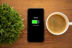 Téléphone de contact avec la batterie chargée sur l'écran photo libre de droits