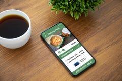 Téléphone de contact avec la nourriture de la livraison d'appli sur l'écran photographie stock libre de droits