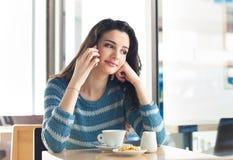 Téléphone de fille appelant au café Photos stock